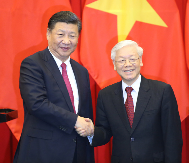 "Chinese President Xi Jinping, also general secretary of the Communist Party of China, and Nguyen Phu Trong, general secretary of the Communist Party of Vietnam, witness the signing of a memorandum of understanding on joint implementation of the Belt and Road Initiative and Vietnam's ""Two Corridors and One Economic Circle"" plan, as well as a series of cooperation documents after their talks in Hanoi, Vietnam, on Nov. 12, 2017. [Photo: Xinhua/Yao Dawei]"