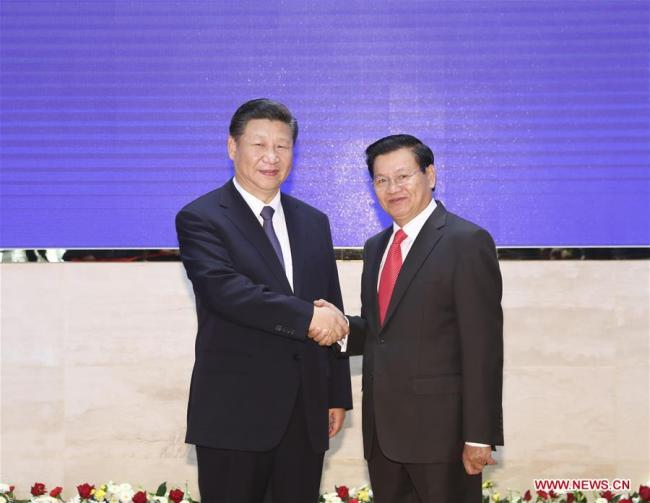 Chinese President Xi Jinping (L), also general secretary of the Communist Party of China Central Committee, shakes hands with Lao Prime Minister Thongloun Sisoulith during their meeting in Vientiane, Laos, Nov. 14, 2017. [Photo: Xinhua]