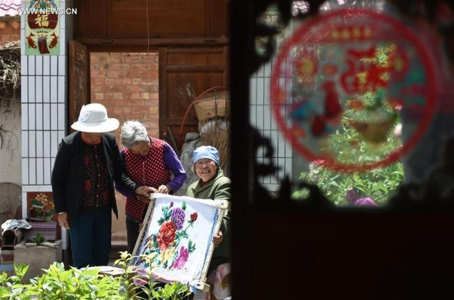 Bu Xilan (R) introduces embroidery skill to neighbours in Maping Village of Longde County, northwest China's Ningxia Hui Autonomous Region, May 23, 2017. Rural embroidery in Longde has a history of more than 100 years. The 67-year-old Bu was awarded as a successor of intangible cultural heritage of Ningxia in 2003. She also taught the skill to her children and neighbours.[Photo: Xinhua]