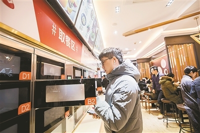 A customer takes his meal from cupboards at an unmanned restaurant of Wufangzhai in Hangzhou, capital city of east China's Zhejiang Province. [Photo: hangzhou.gov.cn]
