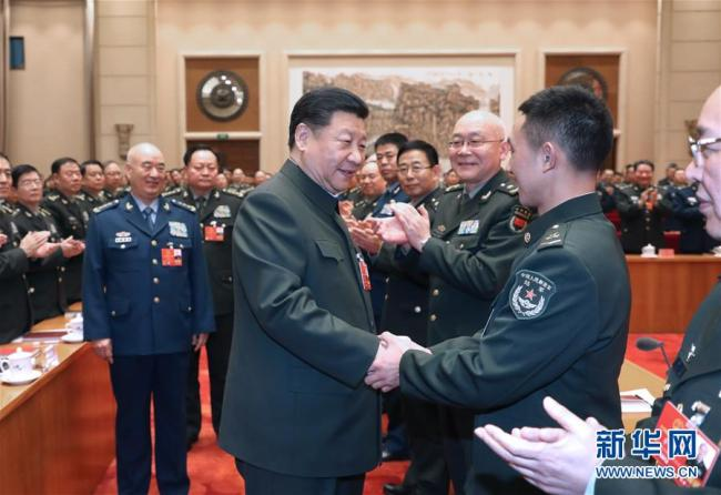Xi Jinping attends a plenary meeting of the delegation of People's Liberation Army and armed police at the ongoing session of the 13th National People's Congress on March 12, 2018. [Photo: Xinhua]