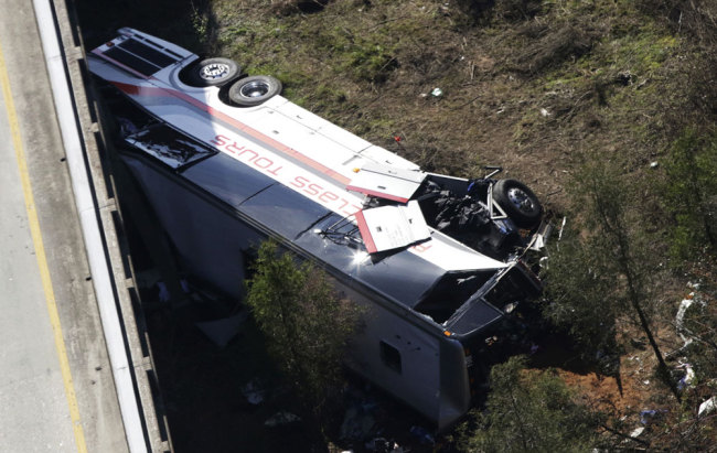 A charter bus sits in a ravine after a deadly crash on Tuesday, March 13, 2018, in Loxley, Ala. The bus carrying Texas high school band members home from Disney World plunged into the ravine before dawn Tuesday. [Photo: AP/Dan Anderson]