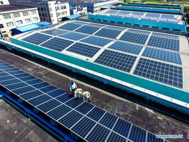 Technicians check solar energy equipment on a roof in Cixi City, east China's Zhejiang Province, May 10, 2017.[Photo: Xinhua]