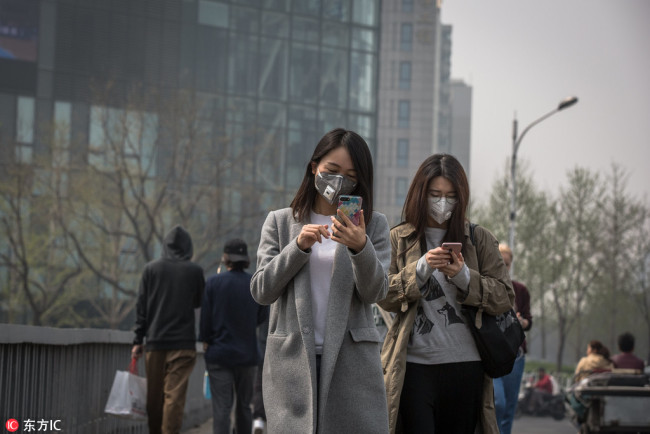 Chinese women wearing protective masks walk on the street during a polluted day in Beijing, China, 02 April 2018.[Photo: IC]