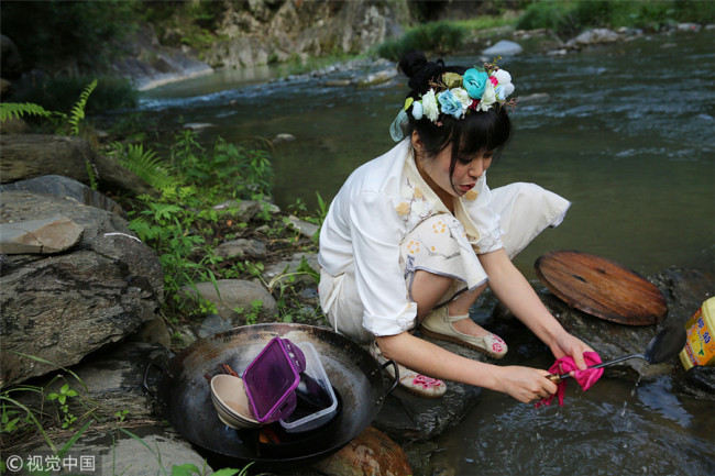 Zhang washes kitchen ware in the brook. [Photo/VCG]