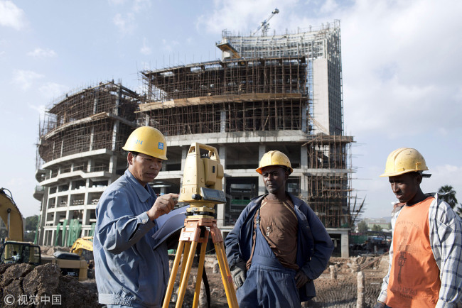 A Chinese construction worker with Ethiopian workers at the new African Union Buildings in Addis Ababa, Ethiopia on October 17, 2010. The building is built for free. [File photo: eyevine/Per-Anders Pettersson]