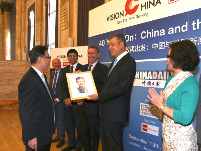 Editor-in-Chief of China Daily Zhou Shuchun (L1) gives gifts to guest speakers at China Daily's Vision China event in London, Sept 13, 2018. [Photo: chinadaily.com.cn]