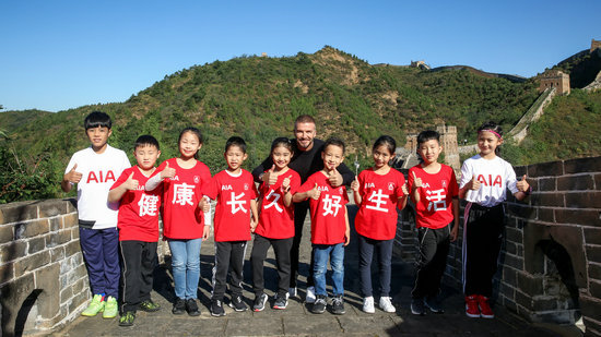 British football star David Beckham and Chinese children at the Great Wall on Sept. 23.[Photo: people.com.cn]