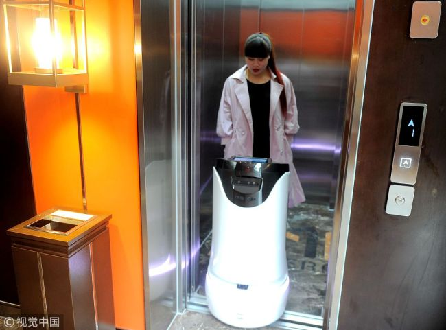 A robot serves a customer at a hi-tech hotel in Chengdu, Sichuan Province on March 20, 2018. [Photo: VCG]