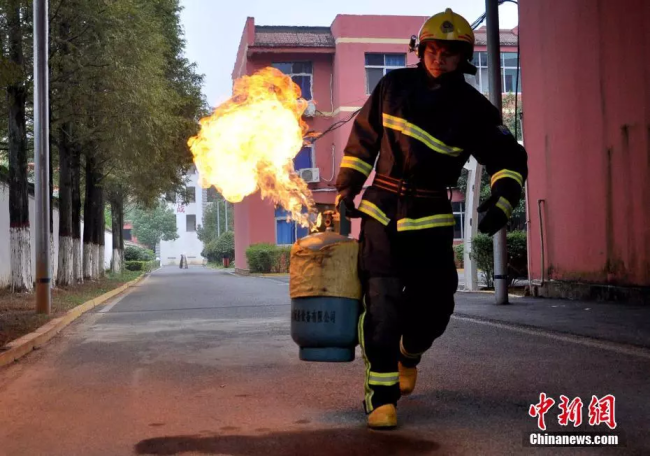 A fireman takes a burning fuel tank away from a residential area. [Photo: Chinanews.com]