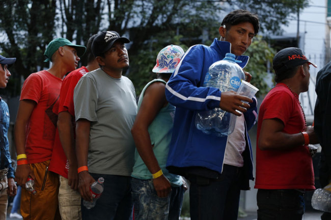 Men line up for donated drinking water, after scores of Central American migrants, representing the thousands participating in a caravan trying to reach the U.S. border, undertook an hours-long march to the office of the United Nations' humans rights body in Mexico City, Thursday, Nov. 8, 2018. [Photo: AP/Rebecca Blackwell]