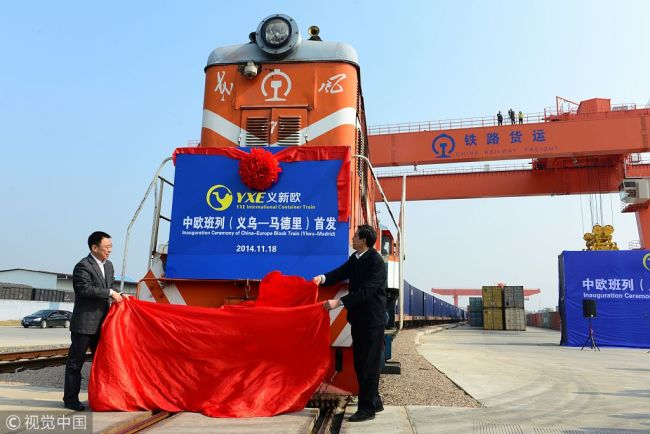 Officials unveil the first YXE international container train travelling between Yiwu and Madrid during an inaugural ceremony at a container terminal in Yiwu city, east China's Zhejiang Province, 18 November 2014. [Photo: VCG]