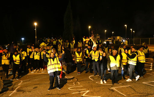 Protesters wearing yellow jackets block a crossroads in Saint-Maximin, southern France, Monday, Nov.19, 2018. The protests reflect broader frustration at President Emmanuel Macron, whose government is sticking to the fuel tax rise as part of efforts to clean up the environment. [Photo:AP]