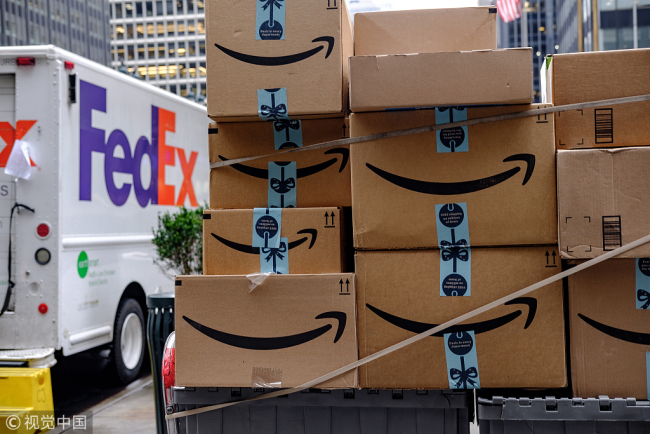 Amazon.com Inc. packages sit in front of a FedEx Corp. delivery truck in New York, U.S., on Monday, Nov. 26, 2018.[Photo: VCG]
