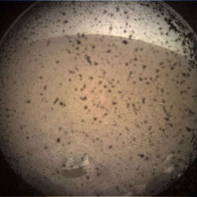 This photo provided by NASA shows the first image acquired by the InSight Mars lander after it touched down on the surface of Mars Monday, Nov. 26, 2018. Debris kicked up by the lander's rockets covers the camera's protective shield, which will later be removed. [Photo: AP]