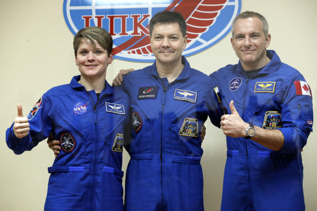 U.S. astronaut Anne McClain, Russian cosmonaut Oleg Kononenko‎ and Canadian astronaut David Saint Jacques pose during a news conference in Russian leased Baikonur cosmodrome, Kazakhstan, Sunday, Dec. 2, 2018. [Photo: AP/Dmitri Lovetsky]