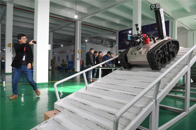 A firefighting robot climbs down stairs during a drill at a factory in Ningde, Fujian Province on Wednesday, December 12, 2018. [Photo: Xinhua]