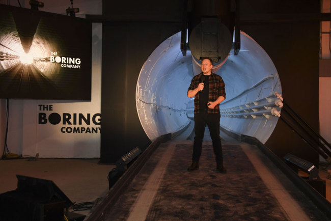 "Elon Musk, co-founder and chief executive officer of Tesla Inc., speaks during an unveiling event for the Boring Co. Hawthorne test tunnel in Hawthorne, Calif., on Tuesday, Dec. 18, 2018. Elon Musk has unveiled his underground transportation tunnel, allowing reporters and VIPs to take some of the first rides in the subterranean tube, which the tech entrepreneur says is the answer to what he calls ""soul-destroying traffic."" [Photo:AP]"