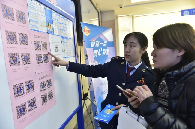 A tax officer explains new tax reduction policies to a taxpayer in Tianjin on December 26, 2018. [File photo: IC]