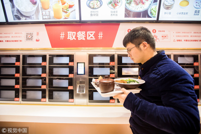 A customer passes the self-service food cabinets at an unmanned restaurant in Hangzhou, Zhejiang Province on January 30, 2018. [File photo: VCG]