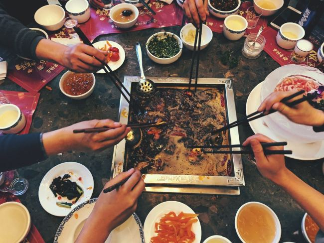 """Hot pot is popular in Sichuan Province. With a history tracing itself to the Warring States Period (475-221BCE), hot pot lets several people share a meal with one large, boiling bowl. Photos show a family sharing a hot pot meal to ring in the """"Year of the Pig,"""" Xichang, Sichuan Province, February 4, 2019. [Photo: China Plus/Jiang Yi]"""