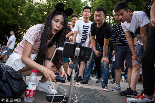 A Chinese webcasting hostess uses a smartphone to make a live webcast during the Douyu festival on May 29, 2017 in Wuhan China.[Photo: VCG]