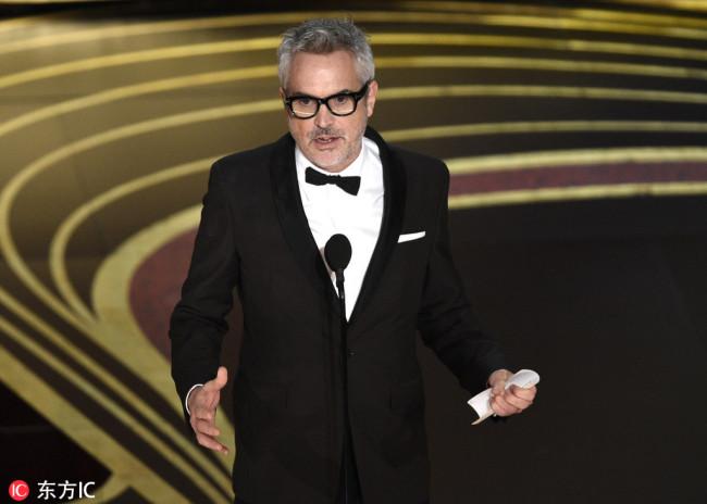 """Alfonso Cuaron accepts the award for best director for """"Roma"""" at the Oscars on Sunday, Feb. 24, 2019, at the Dolby Theatre in Los Angeles. [Photo: AP/Chris Pizzello/Invision via IC]"""