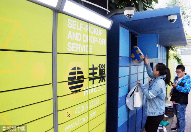 People pick up their parcels from self-service package lockers at a residential area in Changzhou, Jiangsu Province. [Photo: VCG]