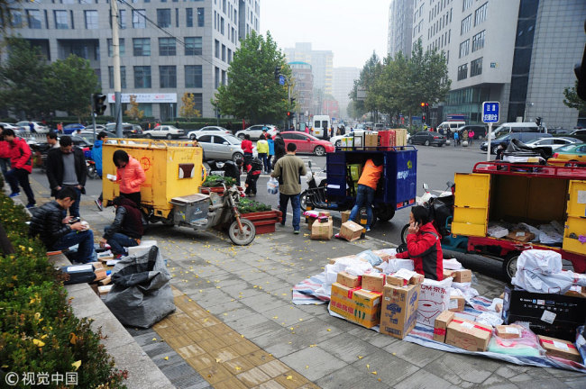Deliverymen wait outside office buildings in Beijing for customers to pick up their parcels. [Photo: VCG]