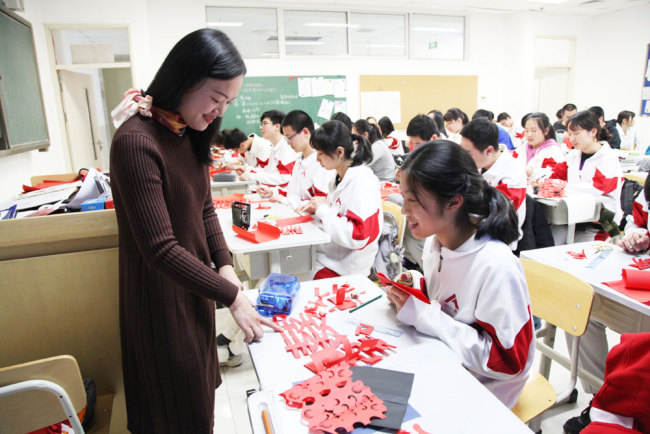 Yan Xiaoyan teaches a student paper-cutting during an elective class on the traditional art form at the High School Affiliated to Renmin University of China in Beijing on Thursday, March 7, 2019. [Photo: China Plus]