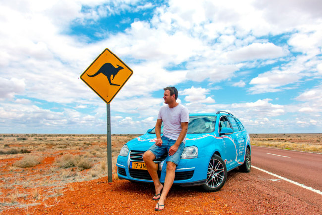 "This handout photo taken on October 28, 2018 and released on April 7, 2019 from Dutch driver Wiebe Wakker (C-R) shows him on the Stuart Highway in the Northern Territory with his retrofitted station wagon nicknamed ""The Blue Bandit"" during his round-the-world trip in the electric car. [Photo: PLUG ME IN PROJECT/Wiebe Wakke/AFP]"