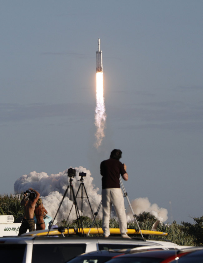 Visitors at Playalinda Beach look on as a SpaceX Falcon Heavy rocket launches from Pad 39B at the Kennedy Space Center in Florida, on April 11, 2019. [Photo: AFP/Gregg Newton]