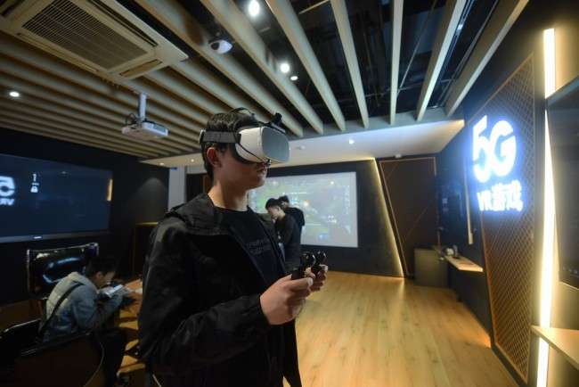 A visitor is wearing a VR headset at a 5G experience hall in Hangzhou, China, April 8, 2019. [Photo:IC]