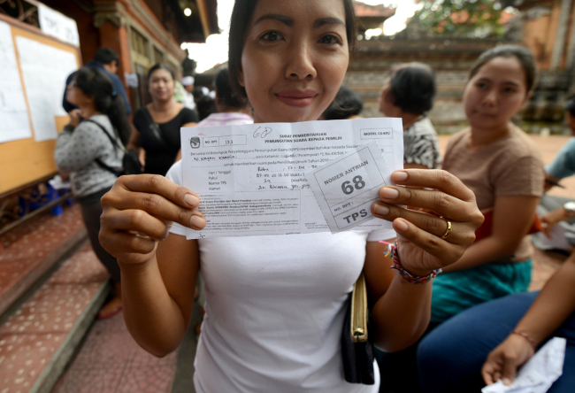 A woman shows her queueing number before casting her vote at a pooling center during the presidential election in Kuta on Indonesia's resort island of Bali on April 17, 2019. Indonesia kicked off one of the world's biggest one-day elections, pitting president Joko Widodo against ex-general Prabowo Subianto in a race to lead the Muslim-majority nation.[Photo: AFP/SONNY TUMBELAKA]