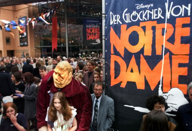 """In this Saturday June 5, 1999 file photo, a girl dressed as Esmeralda carries a dummy of the character Quasimodo as people go into the new concert hall at Potsdamer Platz in Berlin, Germany, before the world premiere of the musical """"The Hunchback of Notre Dame"""" later in the evening. The musical is a co-production of the U.S. American Disney company and the German musical company Stella. [File photo: AP/Jan Bauer]"""