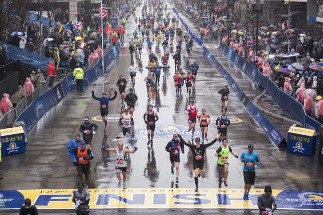 Runners come to the finish line of the 122nd Boston Marathon, where rain and high winds battered down for the duration. Monday April 16, 2018.[Photo: AFP/RYAN MCBRIDE]