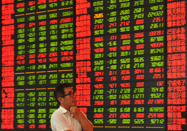 A Chinese investor looks at prices of shares (red for price rising and green for price falling) at a stock brokerage house in Fuyang city, east China's Anhui province.[File Photo: IC]