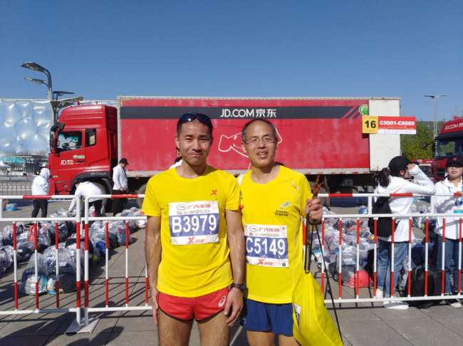 Mori Masatsugu (L) poses for a photo with his friend after they finish a half marathon competition in Beijing on April 4, 2019. [File Photo provided for China Plus]