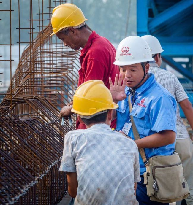 Thirty-nine year old Xu Luping (in blue shirt), now an expert in making precast box-girders, left his rural home at sixteen and has since worked at various construction sites as a migrant worker. [Photo: courtesy of China Tiesiju Civil Engineering Group]