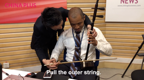 Jin Yue instructed Music Talks host Tony Reid playing the erhu. [Photo by China Plus]