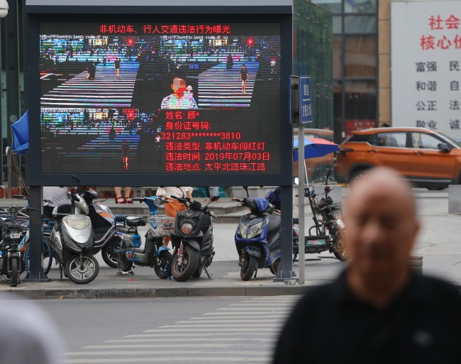 The image of a jaywalker is displayed on a giant screen next to a road in Nanjing. [Photo: IC]