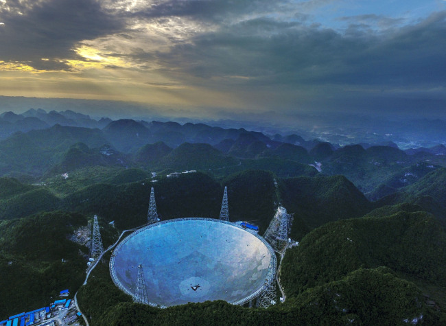 Aerial view of the world's largest radio telescope called FAST (Five-hundred-meter Aperture Spherical Telescope) in Pingtang County, Qiannan Buyi and Miao Autonomous Prefecture, Guizhou Province, June 10, 2016. [File photo: IC]