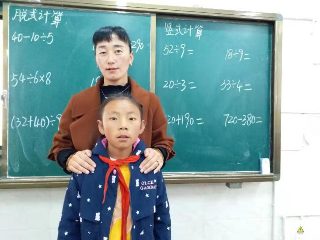 Karma tested positive for congenital heart disease received surgery half a year ago. She was with her math teacher Tenzin in the classroom. [Photo: from China Plus]