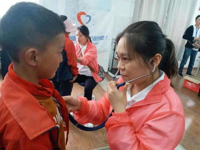 Doctor Li uses a stethoscope to check whether a student has a heart murmur during the screening. [Photo: from China Plus]