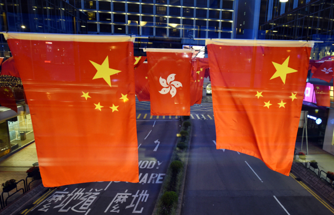 Vehicles drive under flags of China and Hong Kong Special Administrative Region (HKSAR) of the People's Republic of China decorated to mark the 20th anniversary of Hong Kong's return to the motherland in HKSAR on June 25, 2017. [File Photo: IC]