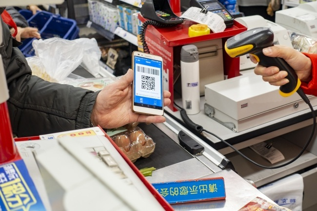 A Chinese cashier scans the QR code through mobile payment service Alipay of Alibaba Group on the smartphone of a customer at a supermarket in Shanghai, China, February 16, 2019. [File Photo: IC]