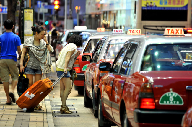 Two women talk to a taxi driver on the street in Hong Kong, China, June 28, 2012. [File Photo: IC]