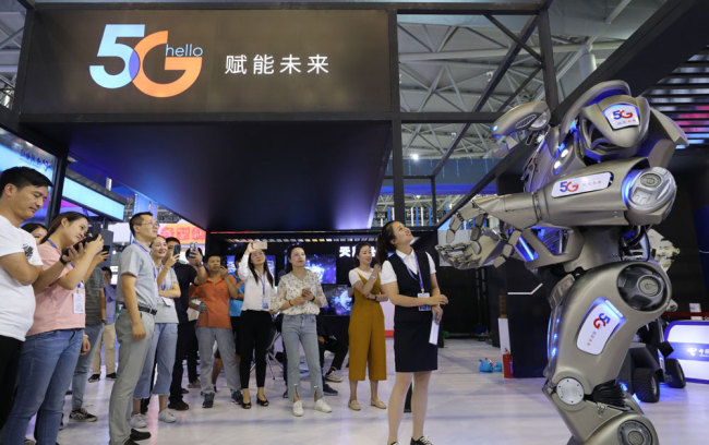People look at a robot developed with 5G technologies at an exhibition of the 2019 World Manufacturing Convention on Thursday, September 19, 2019. [Photo: IC]