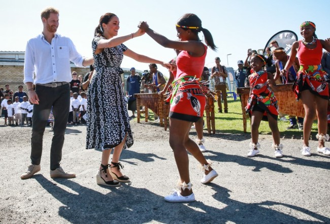 "Prince Harry, Duke of Sussex and Meghan, Duchess of Sussex dance with local girls when visited the ""Justice desk"", an NGO in the township of Nyanga in Cape Town, as they begin their tour of the region on September 23, 2019. [Photo: AFP]"