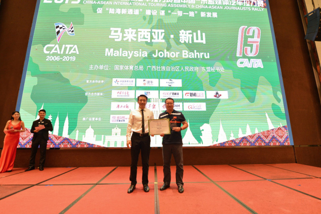 Chinese Motorsports Administration deputy director Yang Guangyu (Left) delivers the top prize award to a race winning team member at the closing ceremony of the China-ASEAN International Touring Assembly in Johor Bahru, Malaysia on Sep 25, 2019. [Photo provided to China Plus]
